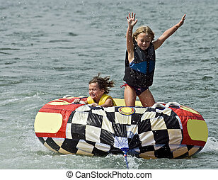 Cute Girls on Tube Behind Boat - Two brave young girls on a...