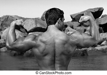 body builder flexing his back by the beach with rocks in the...