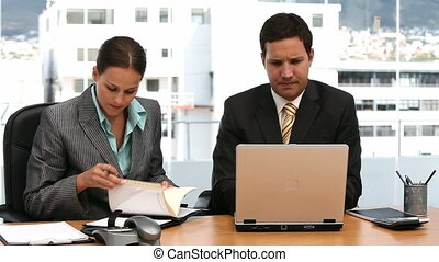 Two serious businesspeople working together in an office