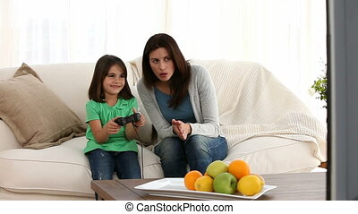Cheerful mom encouraging her daughter to play video games on...