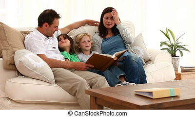 Cute family looking at an album while sitting on the sofa at...