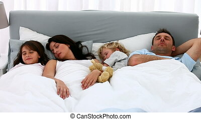 Nice family sleeping together in the morning in the parentss...