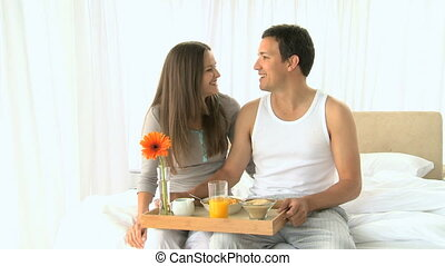 Lovely couple having breakfast in the bedroom at home