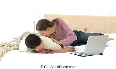 Young couple having fun while working on laptop on their bed