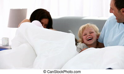 Happy family playing together on a bed