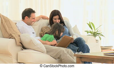 Lovely family looking at a photo album in the living room