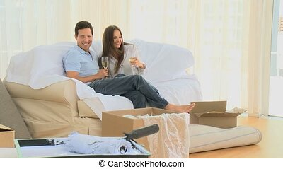 Couple drinking champagne while sitting on the sofa in the...