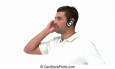 Handsome man listening music standing against a white...