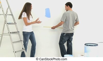 Couple measuring a wall during a renovation of a room at...
