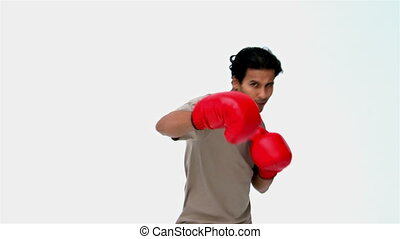 Serious man with boxing gloves against a white background