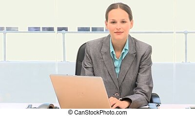 Pretty businesswoman working on a laptop in her office