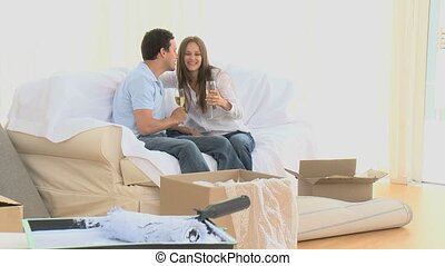 Couple taking a break during the move with glass of white...