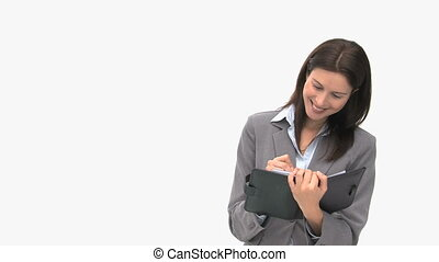 Beautiful businesswoman writing on her agenda isolated on a...