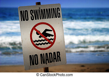 no swimming sign on a beach with waves in the background