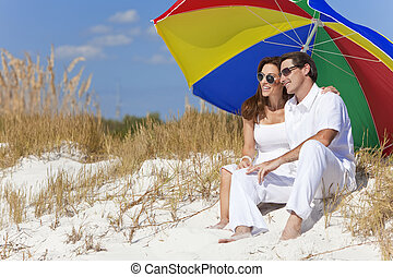 Man & Woman Couple Under Colorful Umbrella on Beach