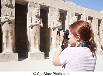 Girl is photographing statues in Karnak temple at Luxor,...