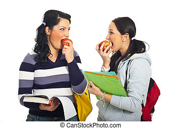 Students girls discuss and eating apples - Two students...
