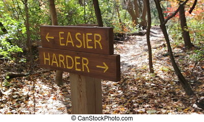 Biker chooses EASIER trail. - Sign in the woods shows two...