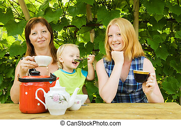 Family having tea at pergola - Family having tea sits at...