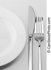 Fork, knife and plate - White plate, knife and fork on light...