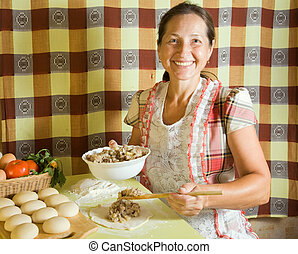 woman cooking meat pasty - elderly woman cooking meat pasty...