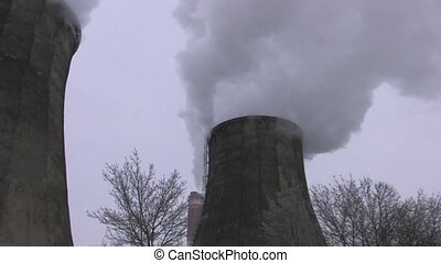 Two smoking towers of power station with trees on...