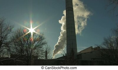 Coal burning power station with trees on foreground at...