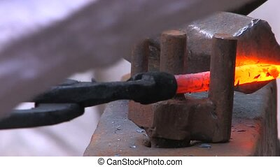 Craftsman working with metal by old fashioned way, with...
