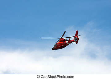 Red Helicopter - A red helicopter flying over a nice blue...