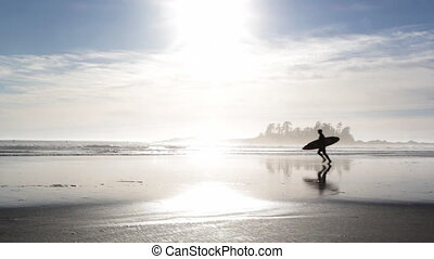 Surfer runs across beach.