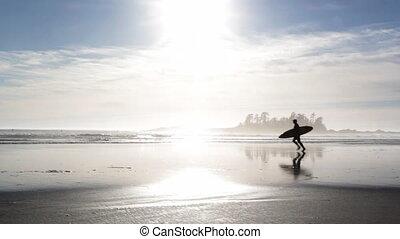 Surfer runs across beach.