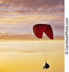 Flight on an operated parachute in twilight on a sunset