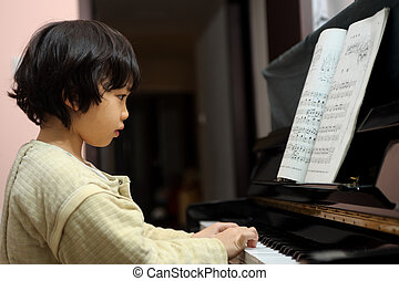Asian kid playing piano - little Asian kid learning to play...