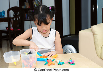 Asian kid playing with dough
