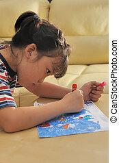 Asian kid drawing at home
