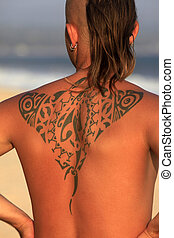 Tattoos - The young man with a beautiful tattoo on a coast...