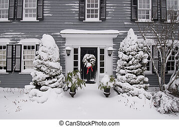 Door entrance to home with holiday wreath and snow