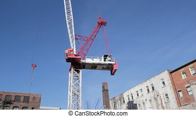 Red crane rotates. Wide. - Red tower crane at construction...
