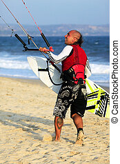 Kitesurfer with surferboard on the beach
