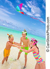 Children flying kite in sea - Three happy children with...