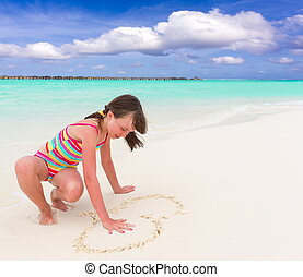 Girl drawing heart on sand - Cute young girl drawing love...