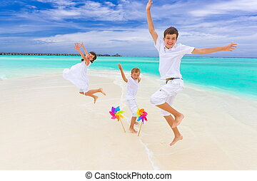 Children jumping on beach - Three happy young children in...