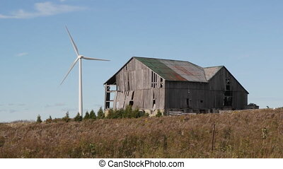 Modern windmill. Old barn. - Modern wind turbine with old...