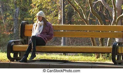 Autumn loneliness - Pretty young Woman sitting on bench