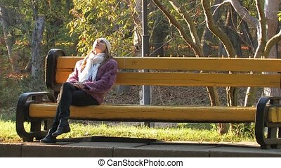 Young girl on park bench - Young Woman sitting on bench on a...