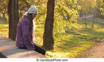 Autumn loneliness in Park - Pretty young Woman in Park on...