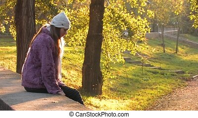 Autumn Solitude - Pretty young Woman in Park on autumn sunny...