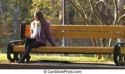 Young Girl resting in park on autumn sunny day