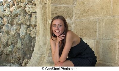 Laughing young lady in Black - Beautiful young Woman sitting...