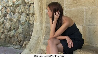 Young Woman in Black - Beautiful young Woman sitting on...